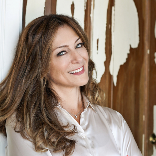 Angela, a woman with brown hair wearing a satin-style off-white shirt and smiling