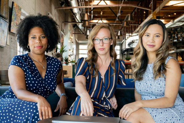 A group of 3 women sitting together in a office setting depicting inclusive culture.